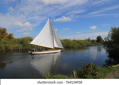 A family enjoying quality time sailing their sailboat on the Norfolk Broads in England on a summer day.