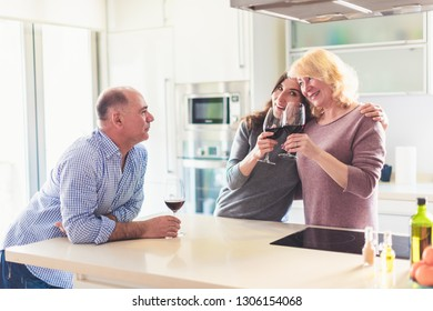 Family enjoying red wine in the kitchen - celebration, friendship and love concept