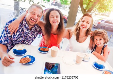 Family Enjoying Snack In Cafe Together.Positive friendly family having breakfast in the coffee shop