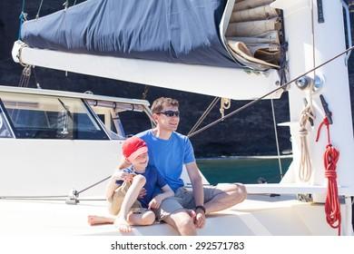 family enjoying summer vacation at sailboat together
