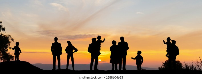 Family enjoying sunset on peak mountain. Silhouette of grandmother and grandchild at hill and looking at sunset, Happy family concept.