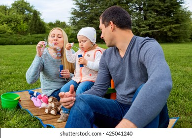 Family enjoying their time with  soap bubbles. Day off with soap bubbles in the park.