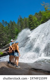 Family enjoying time together by the waterfall. People on hiking trip at High Falls of Dupont State Forest . Blue Ridge Mountains.  Cedar Mountain, North Carolina, USA