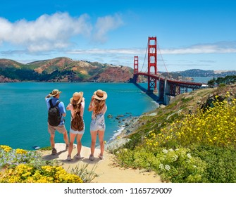 Family enjoying time together on vacation hiking trip.  Golden Gate Bridge, over Pacific Ocean, mountains in the background. San Francisco, California, USA