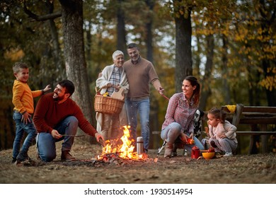 Family enjoying together on picnic making campfire