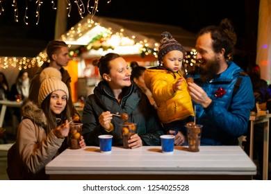 Family enjoying traditional food at Christmas market in Zagreb, Croatia.
