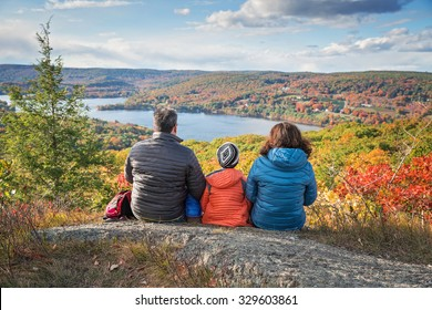 A family enjoying the views after a hike from a beautiful overlook in the fall