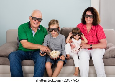 Family Entertaining Watching 3D TV At Home With Kids