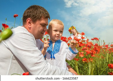 Family in ethnic embroidery ukrainian shirts on the poppies field