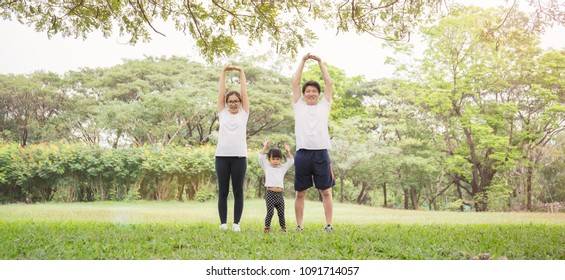 Family exercising jogging together breath fresh air at the park. Group of asian family father mother and daughter stretching after sport. Health care and medical sport fun love family day concept