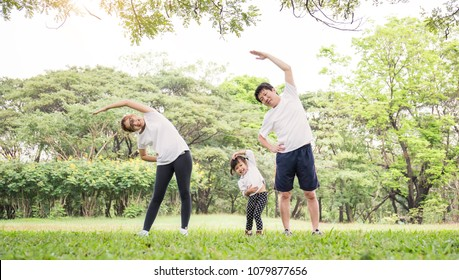 Family exercising and jogging together at the park. Group of asian family father mother and daughter stretching after sport on the grass. Sport health care and medical concept.