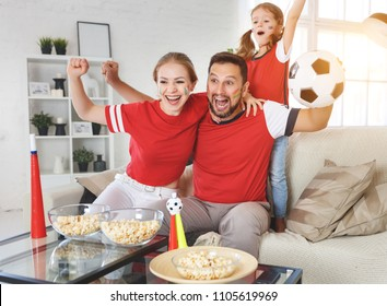 A family of fans watching a football match on TV at home