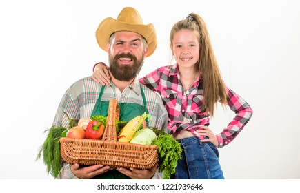 Family farm organic vegetables. Man bearded rustic farmer with kid. Father farmer or gardener with daughter hold basket harvest vegetables. Farmers family homegrown harvest. Gardening and harvesting.