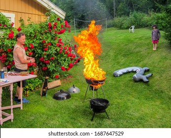 Family, father and child having a outdoor garden barbecue grill party in the backyard. Fail with grill on fire, inferno with big flames.