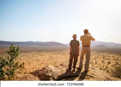 Family of father and child on African safari vacation enjoying view over Samburu Kenya