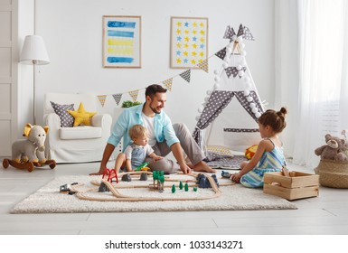family father and children play a toy railway in the playroom