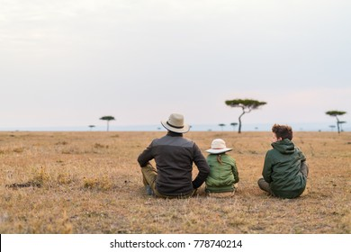 Family of father and kids on African safari vacation enjoying views over Masai Mara in Kenya