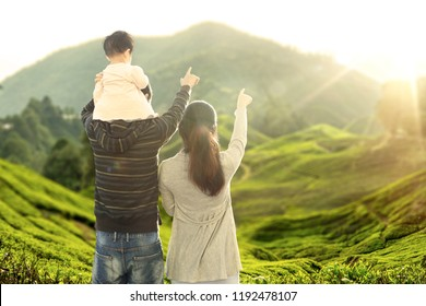 Family, father, mother and baby looking at the sunrise sky. Future with hope concept.