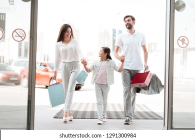 Family, father, mother and daughter with shopping bags are entering shopping mall.