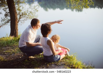 Family - father, mother and daughter, sitting on the Bank back and looking into the distance.