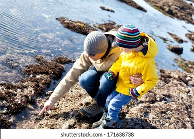family of father and son enjoying tide pools together