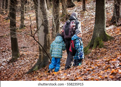 Family, father with two children hiking in forest in winter or early spring.