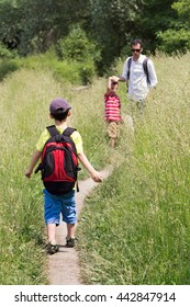 Family of father and two children walking on a path in field or meadow.