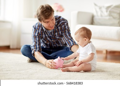 family, fatherhood, finances and parenthood concept - happy smiling young father and little baby playing with piggy bank at home