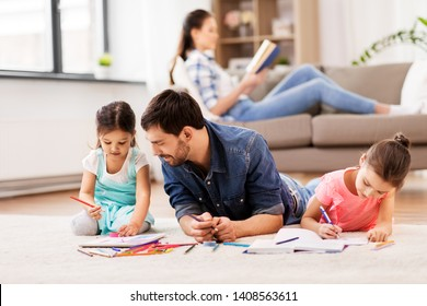 family, fatherhood and leisure concept - father spending time with his little daughters drawing in sketchbooks by crayons and lying on floor at home