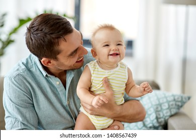 family, fatherhood and people concept - father with little baby daughter at home