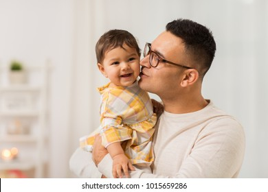 family, fatherhood and people concept - happy father kissing his little baby daughter at home