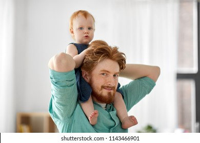 family, fatherhood and people concept - happy red haired father carrying his little baby daughter on neck at home