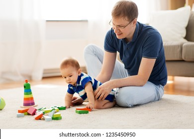 family, fatherhood and people concept - happy father with little baby son playing with toy blocks at home