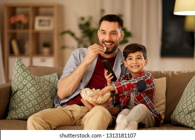 family, fatherhood and people concept - happy father and son with popcorn watching tv at home