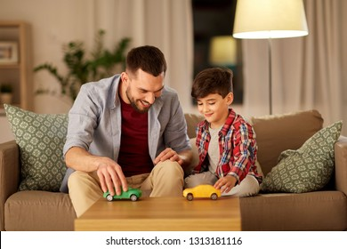 family, fatherhood and people concept - happy father and son playing with toy cars at home in evening