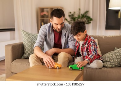family, fatherhood and people concept - happy father and son playing with toy cars at home