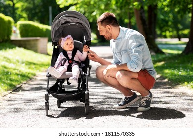 family, fatherhood and people concept - happy father with child in stroller at summer park