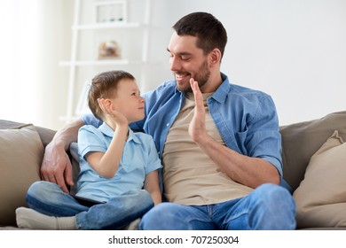 family, fatherhood and people concept - happy father and little son with tablet pc computer doing high five at home