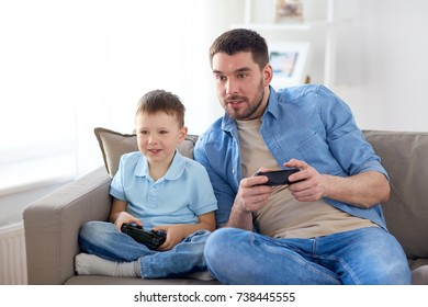 family, fatherhood and people concept - happy father and little son with gamepads playing video game at home