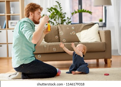 family, fatherhood and people concept - red haired father and little baby daughter playing with soap bubbles at home