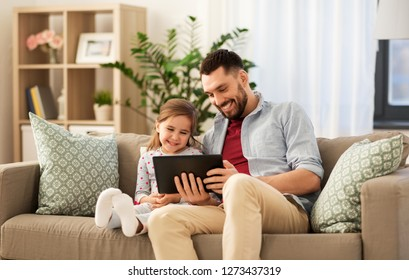 family, fatherhood and technology concept - happy father and little daughter with tablet pc computer at home