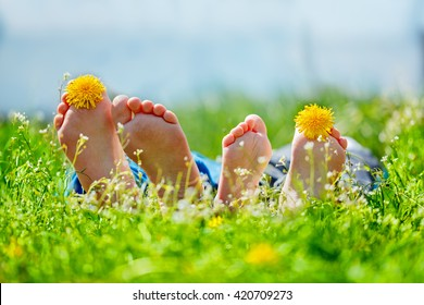 Family feet with dandelion  flowers lying on green grass in sunny day. Concept happy childhood.