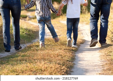 Family feet and legs in jeans. Father, mother, son and daughter walking in an urban neighborhood. Rear view.
