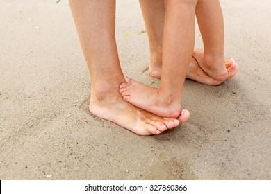 Family feet in the sand on the beach