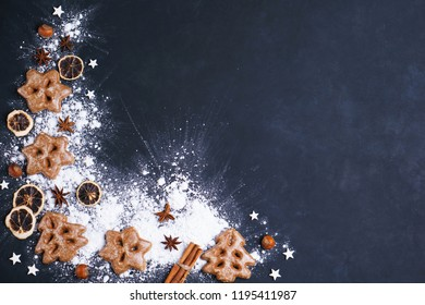 Family festive culinary, Christmas and New Year traditions concept. Gingerbread cookies, baking ingredients and spices on dark background, copy space