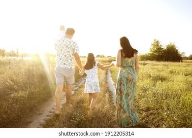 Familie auf einem Feld bei Sonnenuntergang mit dem Rücken in der Rahmenfamilie auf einem Feld bei Sonnenuntergang mit dem Rücken im Rahmen