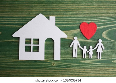 Family figure with a house on green wooden background