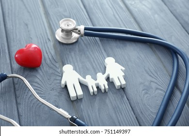 Family figure, red heart and stethoscope on wooden background