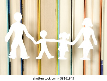 Family figures made from paper with books background, school theme