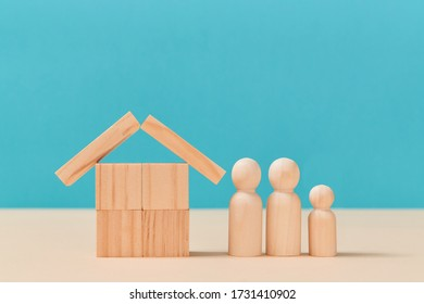 Family figures near house of empty wooden cubes and planks, mockup style. Template for creating design, copy space